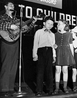 0168761 © Granger - Historical Picture ArchiveWOODY GUTHRIE (1912-1967).   American folk singer, leading children in song at a United Nations event for children, 1948.