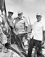 0012655 © Granger - Historical Picture ArchiveERNEST HEMINGWAY   (1899-1961). American writer, center, with Cuban sportsman Elicio Arguilles, Jr., and fishing boat captain Gregorio Fuentes in Cuba during the filming of
