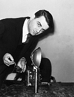 0168594 © Granger - Historical Picture ArchiveEDWIN H. LAND (1909-1991).   American physicist, inventor and founder of the Polaroid Coroporation. Land demonstrating how pictures can be developed instantly with a Speed Graphic camera and a special paper negative. Photograph, 21 Febuary 1947.