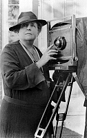 0126349 © Granger - Historical Picture ArchiveFRANCES BENJAMIN JOHNSTON   (1864-1952). American photographer, adjusting the lens of her camera in front of the Arts Club on Eye Street in Washington, D.C., c1936.