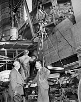 0174313 © Granger - Historical Picture ArchiveHENRY J. KAISER (1882-1967).   American industrialist. Kaiser speaking with Tom Price, the construction manager at a steel mill being built near Fontana, California. In the background is the blask furnace. Photograph, October 1942.