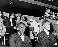 0621343 © Granger - Historical Picture ArchiveELIJAH MUHAMMAD (1897-1975). African American leader of the Nation of Islam. Addressing followers, including Muhammad Ali (born Cassius Clay). Photograph by Stanley Wolfson, 1964.
