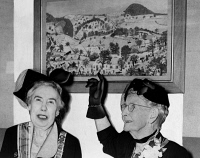 0325318 © Granger - Historical Picture ArchiveGRANDMA MOSES (1860-1961).   Anna Mary Robertson. American folk artist. Donating her painting 'Battle of Bennington' to Mrs. George Kuhner and the Daughters of the American Revolution. Photograph by Roger Higgins, 1953.