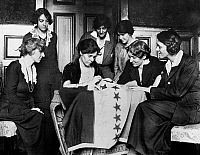 0129405 © Granger - Historical Picture ArchiveALICE PAUL (1885-1977).   American social reformer.   Fellow suffragettes watch Alice Paul sewing another star on the suffragette flag, c1912-1920.