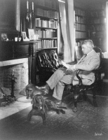0623339 © Granger - Historical Picture ArchiveWILLIAM LYON PHELPS   (1865-1943). American teacher and literary critic. Phelps reading in front of a fireplace with his dog. Photograph by Louis Fabian Bachrach, c1940.