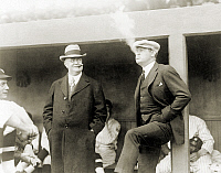 0217021 © Granger - Historical Picture ArchiveJOHNSON & RUTH, 1922.   American baseball executive Ban Johnson (left) smoking cigars at a baseball game in Washington, D.C, with New York Yankees star Babe Ruth, 12 April 1922.