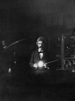 0525827 © Granger - Historical Picture ArchiveMARK TWAIN (1835-1910). Samuel Clemens. American writer and humorist. Photographed in Nikola Tesla's laboratory; an experiment illustrating the lighting of an incandescent lamp by passing the current through the body. Photograph, January 1894.