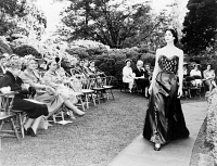 0622736 © Granger - Historical Picture ArchiveEDITH GALT WILSON (1872-1961).   First Lady of President Woodrow Wilson. With a group watching a woman model a gown in a Washington, D.C. garden. Photograph, c1960.