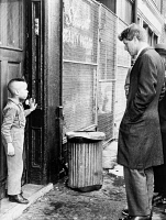 0116068 © Granger - Historical Picture ArchiveROBERT F. KENNEDY   (1925-1968). American lawyer and politician. Senator Kennedy discussing school with a young boy in front of his home on Gates Avenue in the Bedford Stuyvesant neighborhood of Brooklyn. Photographed by Dick DeMarsico, 4 February 1966.