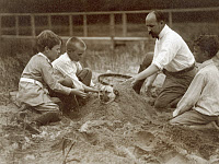 0621828 © Granger - Historical Picture ArchiveROOSEVELT CHILDREN, c1904.   Quentin, Archie, and Nicholas, sons of Theodore Roosevelt, with journalist Walter Russell, burying a dog in sand at Sagamore Hill. Photograph by Edward S. Curtis, c1904.