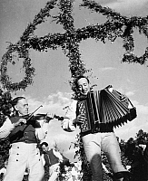 0041015 © Granger - Historical Picture ArchiveSWEDEN: ACCORDIONIST.   An accordionist and a country fiddler playing in front of a maypole on a midsummer eve in Sweden.