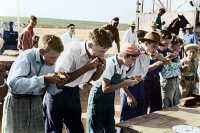 0408976 © Granger - Historical Picture ArchivePIE EATING CONTEST, 1939.   Young men during a pie eating competition at the 4-H Club fair in Cimarron, Kansas. Photograph by Russell Lee, August 1939, digitally colored by Granger, NYC -- All Rights Reserved.
