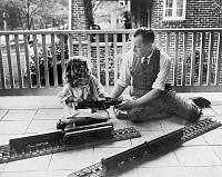0133529 © Granger - Historical Picture ArchiveELECTRIC TRAIN, c1925.   John N. Swartzell and his daughter, Margaret, playing with an electric train on the porch of their home in Washington, D.C., c1925.