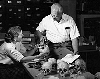 0259027 © Granger - Historical Picture ArchiveARCHAEOLOGY: SKULLS, c1965.   Archaeologist Douglas Osborne and his wife studying human skulls, while working on the Wetherill Mesa project at Mesa Verde National Park. Photograph by Fred Mang, Jr., c1965.