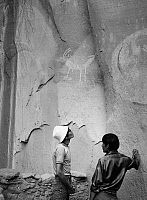 0259031 © Granger - Historical Picture ArchiveNAVAJO NATIONAL MONUMENT.   Two men looking at rock paintings the Betatakin dwelling at the Navajo National Monument in northern Arizona. Photograph by Fred Mang, Jr., c1965.