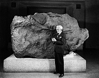 0174232 © Granger - Historical Picture ArchiveAHNIGHITO METEORITE, c1940.   Astronomer Dr. Clyde Fisher standing next to the Ahnighito meteorite in the Hayden Planetarium at the American Museum of Natural History in New York City, New York. Photograph, c1940.