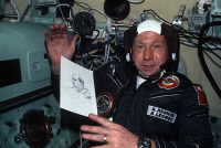 0407660 © Granger - Historical Picture ArchiveAPOLLO-SOYUZ, 1975.   Russian cosmonaut Aleksey Leonov in the Soyuz Orbital Module holding a drawing of American astronaut Thomas Stafford during the Apollo-Soyuz Test Project. Photograph, July 1975.