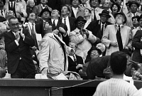0170402 © Granger - Historical Picture ArchiveBASEBALL CROWD, 1962.   President John F. Kennedy ducks out of sight (right, behind ball player) as a foul ball hit by Willie Tasby came towards him during a game between the Washington Senators and the Detroit Tigers, 9 April 1962. At right, just behind the president, is Secretary of the Treasury Douglas Dillon. At far left is Vice President Lyndon Johnson.