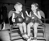 0117321 © Granger - Historical Picture ArchiveJUNIOR BOXER, 1939.   Dorothy Wood, age 5, laces the boxing gloves of her companion, Chuck Andrews, age 3, at the U.S. Naval Academy's 20th Annual Junior Boxing Championships, in Annapolis, Maryland, 1939.