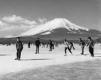 0186507 © Granger - Historical Picture ArchiveJAPAN: ICE SKATING, c1963.   Ice skaters on Lake Yamanaka in Japan, with Mount Fuji in the background. Photograph, c1963.