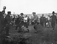0068133 © Granger - Historical Picture ArchiveOLYMPICS: LONDON, 1908.   An exhausted Dorando Pietri of Italy (1885-1942) being assisted by judges across the finish line in the marathon event at the 1908 Olympic Games in London, for which assistance he would be disqualified from winning the gold medal, though he was the first runner to finish the race.