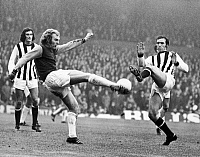 0131260 © Granger - Historical Picture ArchiveSOCCER MATCH, 1971.   Bobby Moore of West Ham United kicks the ball away from Jeff Astle of West Bromwich Albion during a soccer match, 1971.