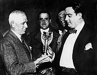 0167127 © Granger - Historical Picture ArchiveWORLD CUP: TROPHY, 1930.   Jules Rimet (left), president of FIFA (Federation Internationale de Football), presents the first World Cup trophy to Dr. Paul Jude, president of the Uruguayan Football Association, after Uruguay's victory over Argentina, 30 July 1930.