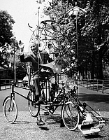 0120856 © Granger - Historical Picture ArchiveEMETT: LUNACYCLE, 1970.   British cartoonist and inventor Rowland Emett, riding his 'Lunacycle,' which he claims can be ridden as a bicycle on Earth and soft landed on the moon. The invention allows space for a cat for companionship and for catching moon mice, a fly-swatter for swatting meteorites away, and a sun shield. Photograph, 1970.