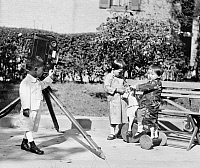 0124484 © Granger - Historical Picture ArchiveCHILDREN AND CAMERA, c1919.   The children of Chinese diplomats V.K. Wellington Koo and Tsannyuen Phillip Sze, playing with a camera on a tripod. Photograph, c1919.