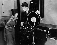 0174676 © Granger - Historical Picture ArchiveFILMMAKING: SOUND, 1930.   Sound engineer Douglas Shearer demonstrating sound recording for actress Norma Shearer. Photograph, 1930.