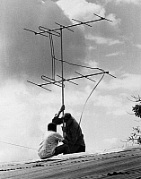 0176066 © Granger - Historical Picture ArchiveCOLOMBIA: TV ANTENNA.   An American Peace Corps volunteer installing a television antenna on a rooftop in Colombia. Photographed by Charles Marden Fitch, c1965.