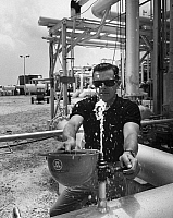 0175603 © Granger - Historical Picture ArchiveWATER PURIFICATION, 1967.   Robert Bailie, manager of the water desalination plant constructed at Stock Island in Key West, Florida, by the Westinghouse Electric Corporation, using his hard hat to catch a sample of desalinated water shortly after the plant's opening in 1967.