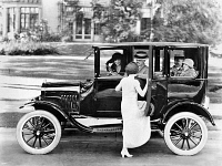0042532 © Granger - Historical Picture ArchiveFORD SEDAN, c1923.   A woman getting into a Ford Sedan with four other passengers. Photograph, c1923.