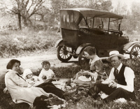 0171711 © Granger - Historical Picture ArchiveFAMILY PICNIC, c1918.   A family having a picnic on the side of a road, with a Model T Ford in the background. Photograph, c1918.