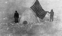 0131985 © Granger - Historical Picture ArchiveNORTH POLE: IGLOO, c1909.   Two members of Frederick Cook's journey expedition at the North Pole with a U.S. flag in an igloo at the campsite. Photograph, c1909.