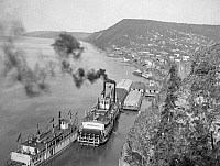 0119737 © Granger - Historical Picture ArchiveALASKA: WATERFRONT.   Aerial view of riverboats on the Yukon River, cliffs and a town in the distance, Ruby, Alaska. Photograph, c1900-1923.