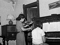 0122265 © Granger - Historical Picture ArchiveCHICAGO: MUSIC, 1941.   Two girls playing violin and piano in their home in Chicago, Illinois. Photograph by Russell Lee, April 1941.