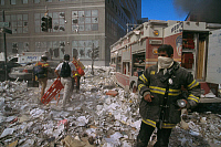 0170009 © Granger - Historical Picture ArchiveNEW YORK: SEPTEMBER 11TH.   A firefighter and a rescue team on a litter-covered street in lower Manhattan, after the terrorist attack on the World Trade Center on 11 September 2001.