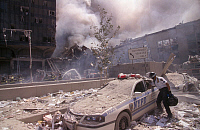 0170014 © Granger - Historical Picture ArchiveNEW YORK: SEPTEMBER 11TH.   A police officer reaching into a debris and ash-covered police car in lower Manhattan, after the terrorist attack on the World Trade Center on 11 September 2001.