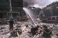 0170016 © Granger - Historical Picture ArchiveNEW YORK: SEPTEMBER 11TH.   A team of firefighters extinguish a fire on a debris-covered street in lower Manhattan, after the terrorist attack on the World Trade Center on 11 September 2001.