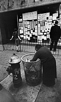 0175073 © Granger - Historical Picture ArchiveLOWER EAST SIDE, c1970.   A woman picking through a garbage can on the street on the Lower East Side in New York City. Photograph, c1970.