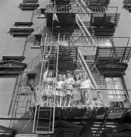 0323848 © Granger - Historical Picture ArchiveNEW YORK: MOTT STREET, 1942.   Italian-American women on a fire escape watching a parade and flag raising ceremony on Mott Street in New York City, in honor of men from the neighborhood in the United States Army. Photograph by Marjory Collins, 1942.