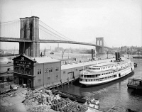 0409535 © Granger - Historical Picture ArchiveBROOKLYN BRIDGE, c1905.   Steamboat parked at a marine terminal next to the Brooklyn Bridge, New York. Photograph, c1905.