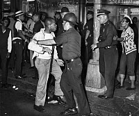 0621340 © Granger - Historical Picture ArchiveBROOKLYN: RIOTS, 1964.   A confrontation between protesters and police at the corner Fulton Street and Nostrand Avenue in Bedford-Stuyvesant, Brooklyn, during the riots that took place after the fatal shooting of African-American teenager James Powell by NYPD Lieutenant Thomas Gilligan. Photograph by Stanley Wolfson, 21 July 1964.