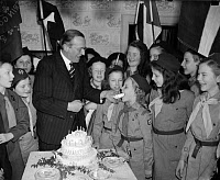 0170513 © Granger - Historical Picture ArchivePHILIP KERR AND GIRL SCOUTS.   British ambassador to the United States, Philip Henry Kerr, 11th Marquess of Lothian, celebeates the 28th anniversary of the founding of the Girl Scouts at a party in Washington, DC. Kerr is feeding a piece of cake to 11-year-old Girl Scout Winifred McGowan of Troop 138. Photograph, 12 March 1940.