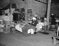 0323370 © Granger - Historical Picture ArchiveRED CROSS INFIRMARY, 1937.  A sick flood refugee in the Red Cross temporary infirmary at a flood refugee camp in Forrest City, Arkansas. Photograph by Walker Evans, February 1937.