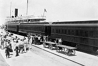 0132509 © Granger - Historical Picture ArchiveKEY WEST: TRAIN & SHIP.   A passenger train in Key West, Florida, where a ship arriving from Cuba is docked. Photograph, c1930.
