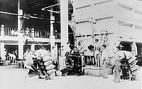 0118192 © Granger - Historical Picture ArchiveHAWAII: SUGAR MILL, c1915.   Filling, weighing and sewing sacks of raw sugar at a plantation mill in Hawaii. Photograph, c1915.