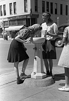 0121262 © Granger - Historical Picture ArchiveWATER FOUNTAIN, 1941.   Two girls drinking from a public water fountain on a street corner of Caldwell, Idaho. Photograph by Russell Lee, July 1941.