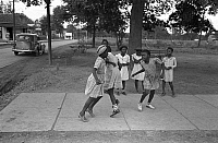 0121699 © Granger - Historical Picture ArchiveGIRLS PLAYING, 1938.   A group of African American girls playing on a rural sidewalk in Lafayette, Louisiana. Photograph by Russell Lee, October 1938.